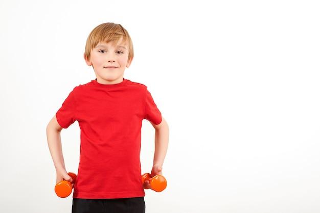 Schuljungen-training mit hanteln, lokalisiert auf weiß. körperliches training für kinder. gesunde kindheit. fitness für kinder. speicherplatz kopieren.