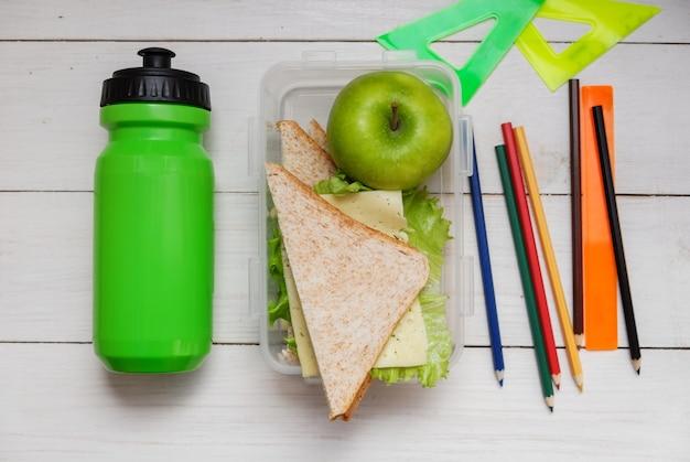 Schuljungenfrühstück auf weißem holztisch. sandwich mit käse und schinken und salatblatt, grüne flasche wasser. lineale und bleistifte