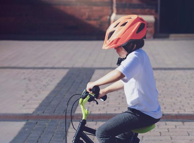 Schuljungenreitfahrrad in einem sturzhelm, geerntetes schusskind lernt, fahrrad im park, offenes foto zu fahren kind im sturzhelm, der ein radfahren auf die straße reitet.