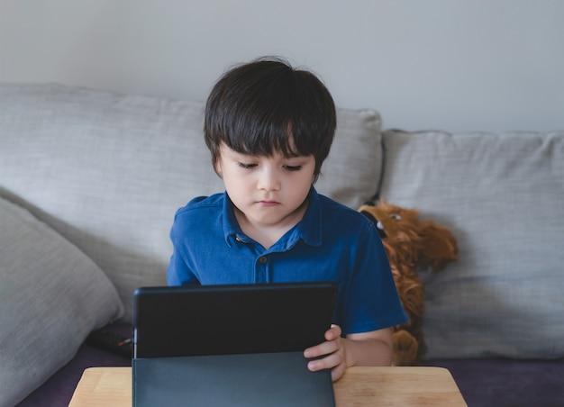 Schulkind, das tablette für seine hausaufgaben verwendet, kind, das digitales tablett mit denkendem gesicht betrachtet, junge, der cartoon auf touchpad sieht, neuer normaler lebensstil mit online-lernen, fernunterricht