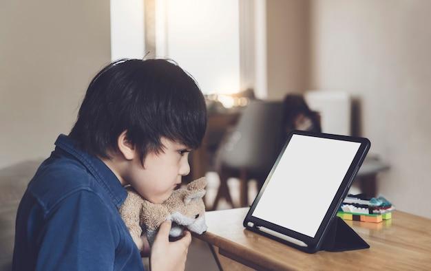 Schulkind, das tablette für seine hausaufgaben verwendet, kind, das digitales tablett mit denkendem gesicht betrachtet, junge, der zeichentrickfilm auf touchpad sieht, nw normales leben mit online-lernen, fernunterricht