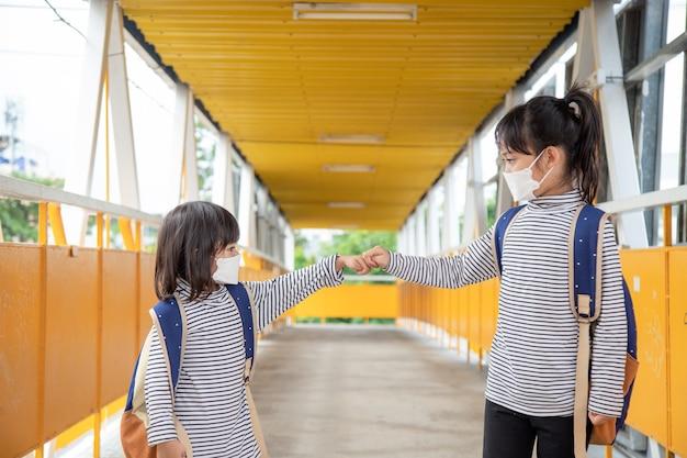 Schulkind, das während des ausbruchs des coronavirus eine gesichtsmaske trägt kleines mädchen, das wieder zur schule geht
