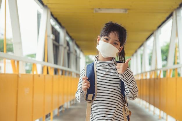 Schulkind, das während des ausbruchs von coronavirus und grippe eine gesichtsmaske trägt