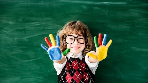 Schulkind in der klasse glückliches kind gegen grüne tafel bildungskonzept