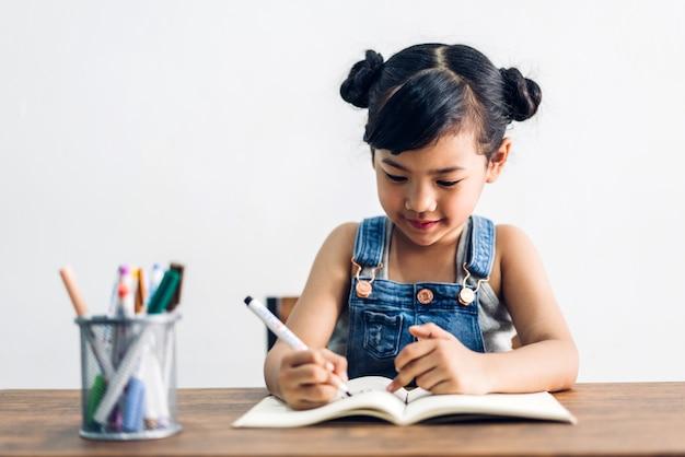 Schulkind kleines mädchen lernen und schreiben in notizbuch mit bleistift machen hausaufgaben zu hause. bildungskonzept