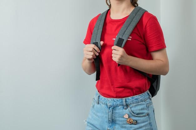 Schulkind mit einem grauen rucksack in den schultern