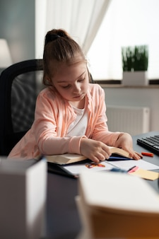 Schulkind sitzt am schreibtisch im wohnzimmer und hält hausaufgabenheft