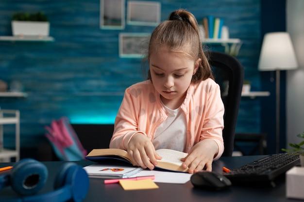 Schulkind sitzt am schreibtisch im wohnzimmer und hält schulbuch