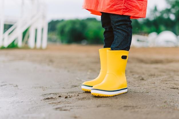 Schulkind trägt gelbe gummistiefel am strand kind steht im sand in wasserdichtem gummi