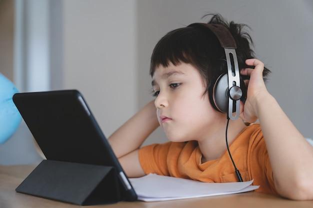 Schulkind trägt kopfhörer und hört dem lehrer in der online-klasse zu