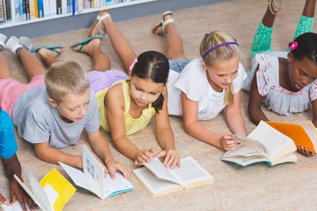 Schulkinder, die auf dem boden liegen und buch in der bibliothek lesen