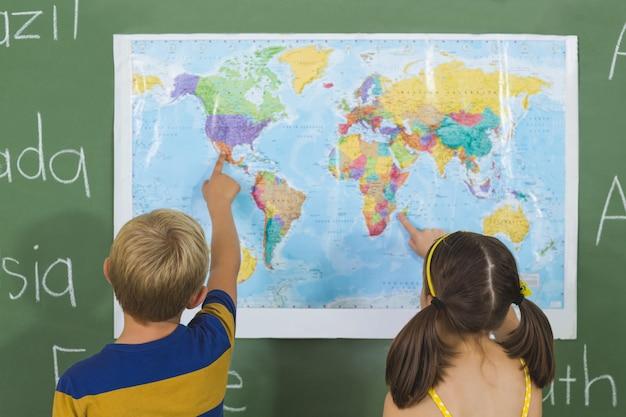 Schulkinder, die auf karte im klassenzimmer zeigen