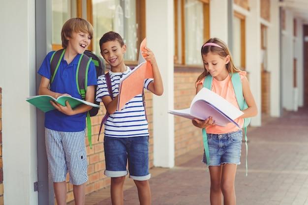 Schulkinder, die bücher beim gehen in korridor lesen