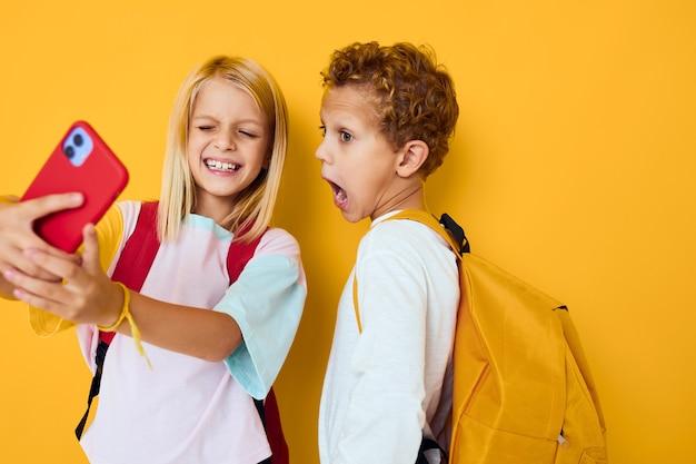 Schulkinder, die den gelben hintergrund der telefonunterhaltungskommunikation betrachten