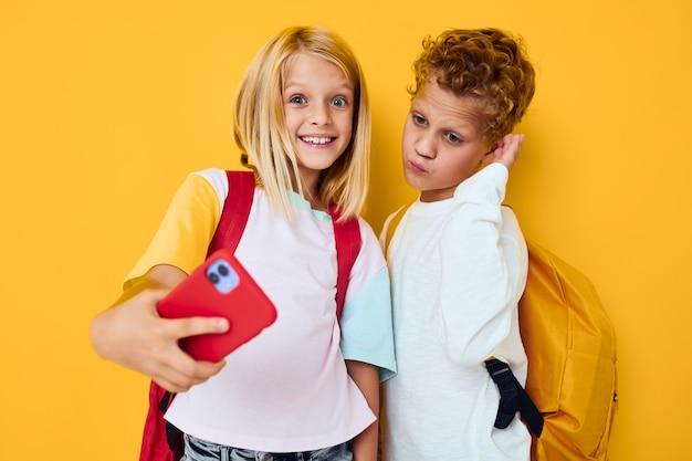 Schulkinder, die den isolierten hintergrund der telefonunterhaltungskommunikation betrachten