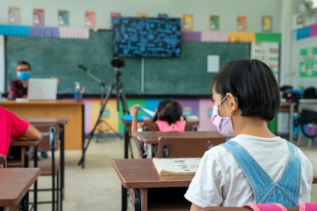 Schulkinder, die eine medizinische gesundheitsmaske tragen, die im klassenzimmer an der grundschule sitzt.