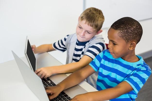 Schulkinder, die einen laptop und eine digitale tablette im klassenzimmer verwenden