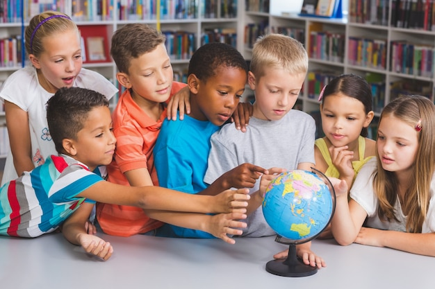 Schulkinder, die globus in bibliothek betrachten