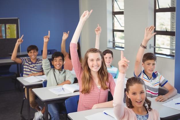 Schulkinder, die hand im klassenzimmer an der schule erheben