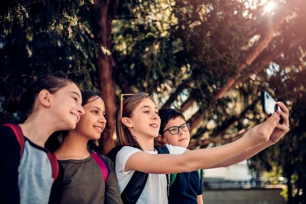 Schulkinder, die im schatten sitzen und selfie auf der straße nehmen