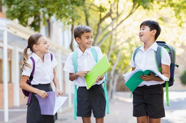 Schulkinder, die miteinander beim lesen von büchern im campus sprechen