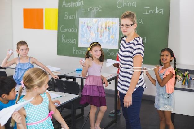 Schulkinder, die weibliche lehrerin mit seil im klassenzimmer binden