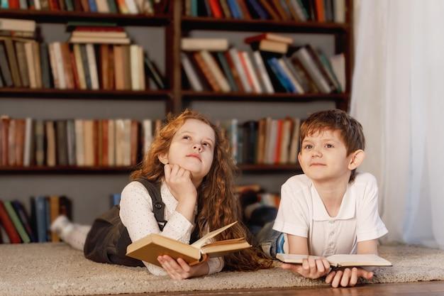 Schulkinder, die zu hause das buch träumen und lesen.