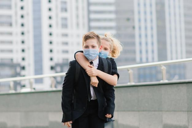 Schulkinder, ein junge und ein mädchen in medizinischen masken gehen durch die stadt.