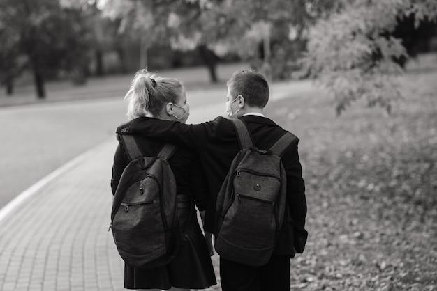 Schulkinder, ein junge und ein mädchen in medizinischen masken gehen im stadtpark spazieren.