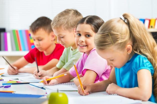 Schulkinder im klassenzimmer schreiben, zeichnen