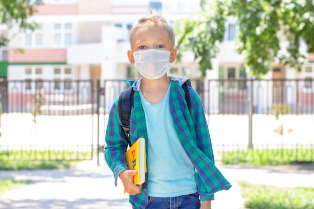 Schulkinder in einer schutzmaske mit einem rucksack und einem lehrbuch in den händen. in einem t-shirt und einem karierten shirt