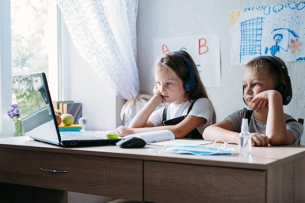 Schulkinder jungen und mädchen mit laptop für online-lernen während des homeschooling zu hause homeschooling