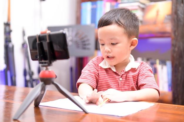 Schulkinder lernen lektion mit handy zu hause, online-lernen zu hause