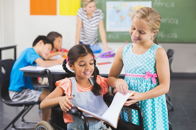 Schulkinder lesen buch im klassenzimmer