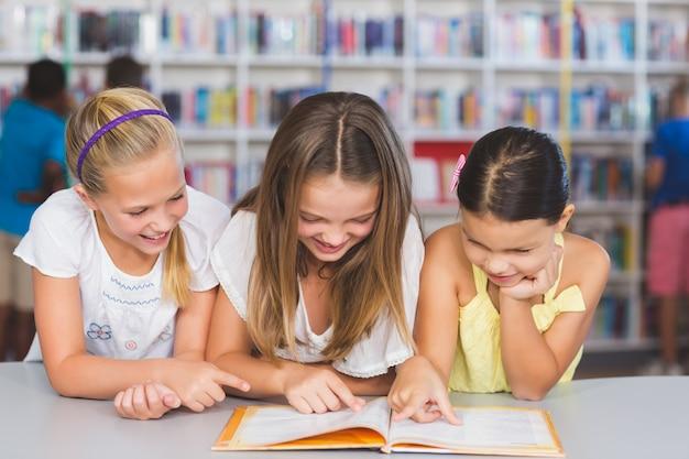 Schulkinder lesen zusammen buch in der bibliothek