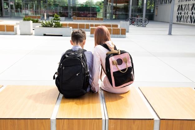 Schulkinder mädchen und junge sitzen mit schulrucksäcken auf einer holzbank zwischen betonwänden mit rucksäcken auf dem rücken, rückansicht