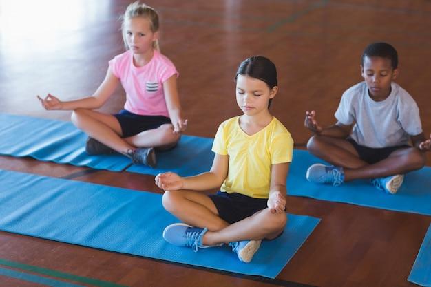 Schulkinder meditieren während des yoga-unterrichts