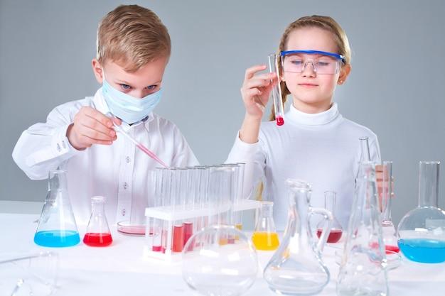 Schulkinder mischen von flüssigkeiten