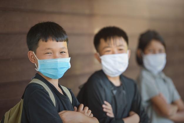 Schulkinder mit schutzmaske gegen grippeviren im unterricht im klassenzimmer