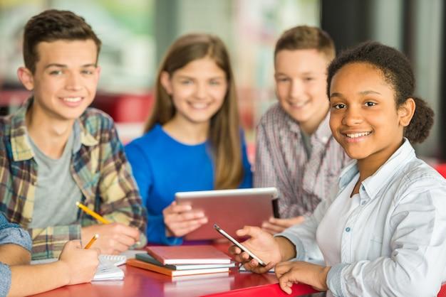 Schulkinder sitzen in einem café und lernen unterricht.
