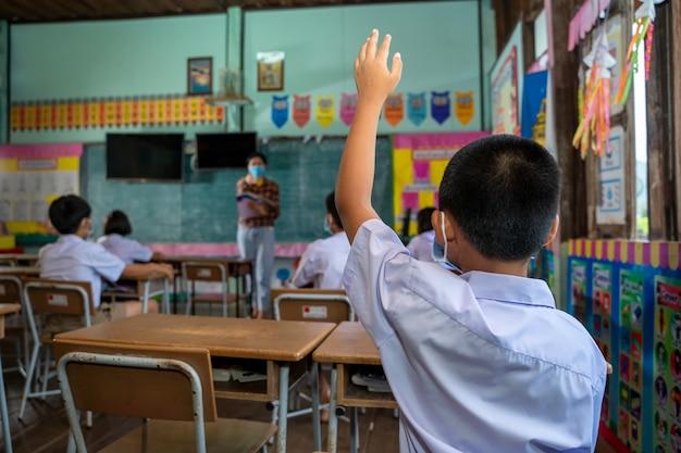 Schulkinder tragen gesichtsmaske, gruppe von schulkindern mit lehrer, der im klassenzimmer sitzt und hände hebt,