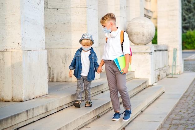 Schulkinder tragen gesichtsmaske während des coronavirus-ausbruchs. kinder gehen nach der schule nach hause.
