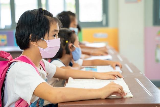 Schulkinder tragen schützende gesichtsmasken, um die sicherheit in der grundschule, das bildungs-, lern- und personenkonzept social distancing zu gewährleisten.