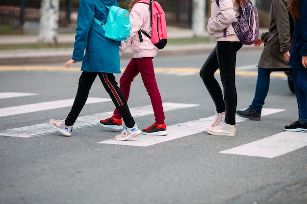 Schulkinder überqueren die straße in medizinischen masken. kinder gehen zur schule.
