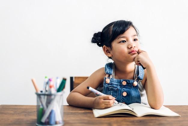 Schulkindermädchen, das auf notizbuch mit bleistift lernt und hausaufgaben macht