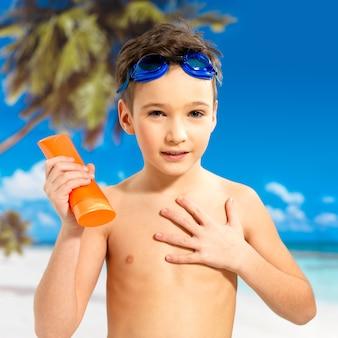 Schulkindjunge, der sonnenschutzcreme auf den gebräunten körper anwendet