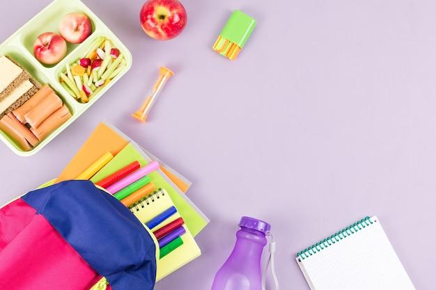 Schulkonzept flach. kinderrucksack, lunchbox, wasserflasche, notizbuch, marker auf holzdesktop
