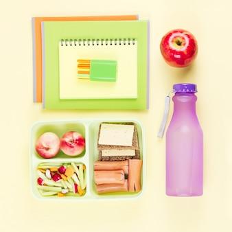 Schulkonzept flach mit lunchbox, wasserflasche und schulbedarf für kinder