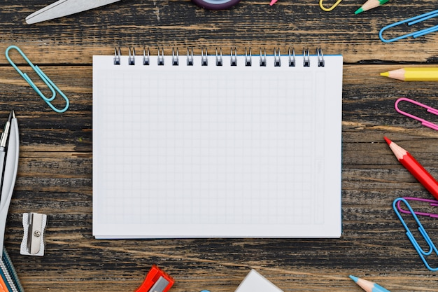 Schulkonzept mit notizbuch, schulmaterial auf holztischnahaufnahme.