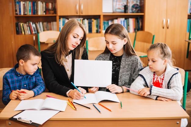 Schullehrer, der mit schülern am schreibtisch arbeitet